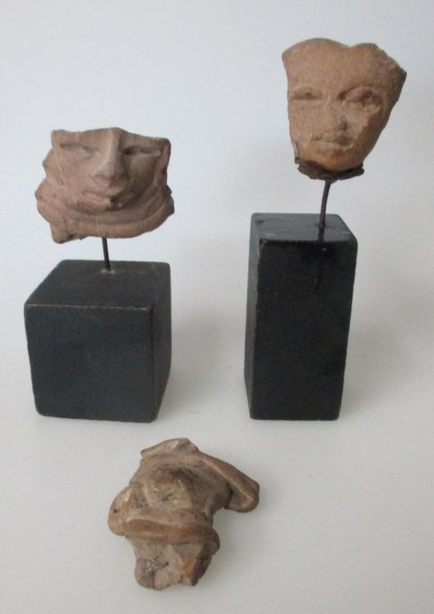 Collection of three ancient South American clay figurines with faces.