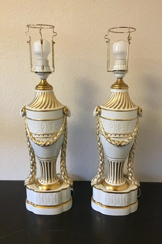 Royal Copenhagen A pair of baluster-shaped lamps on base decorated with garlands, Ram heads and gold. With Juliane Marie Stamp from 1905-12. Mounted with EL bulbs and wire.