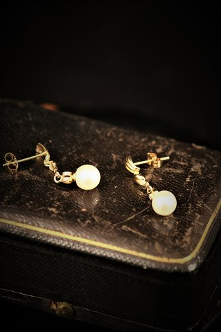 A pair of earrings in 14 carat gold with freshwater pearl.