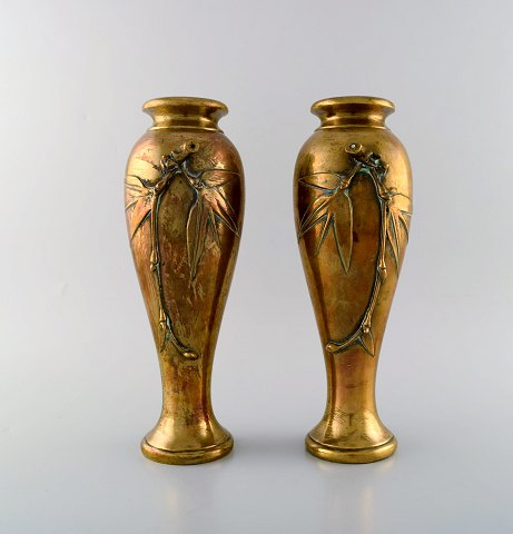 A pair of French art nouveau bronze vases with flowers in relief. Ca. 1890.